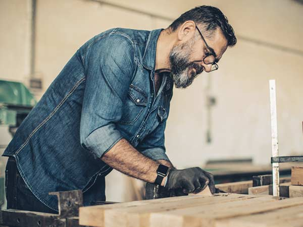 Mature male doing woodworking in a workshop while wearing glasses