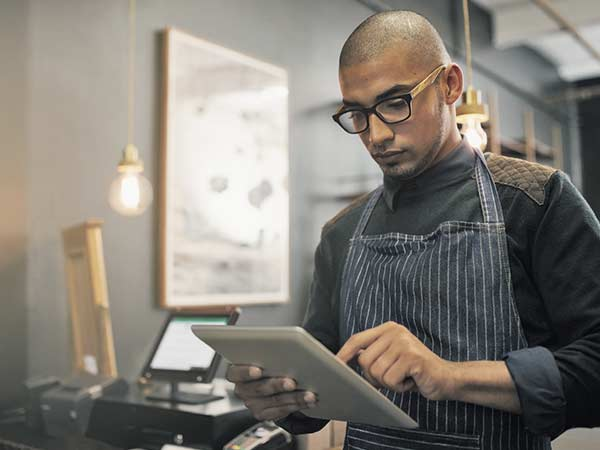 Young man in a small business, wearing glasses and working on a tablet device