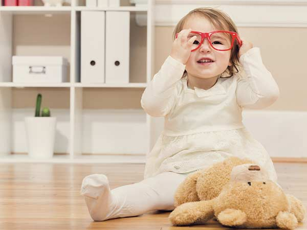 Little girl sitting on the floor with her teddy bear while playing with her glasses