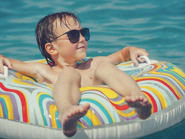 Kid sitting in a tube in the swimming pool while wearing sun glasses