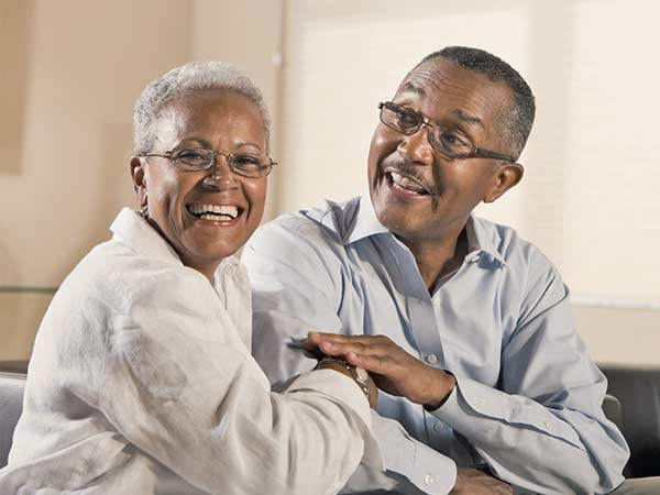 Mature African-American couple, wearing glasses and sitting on the sofa
