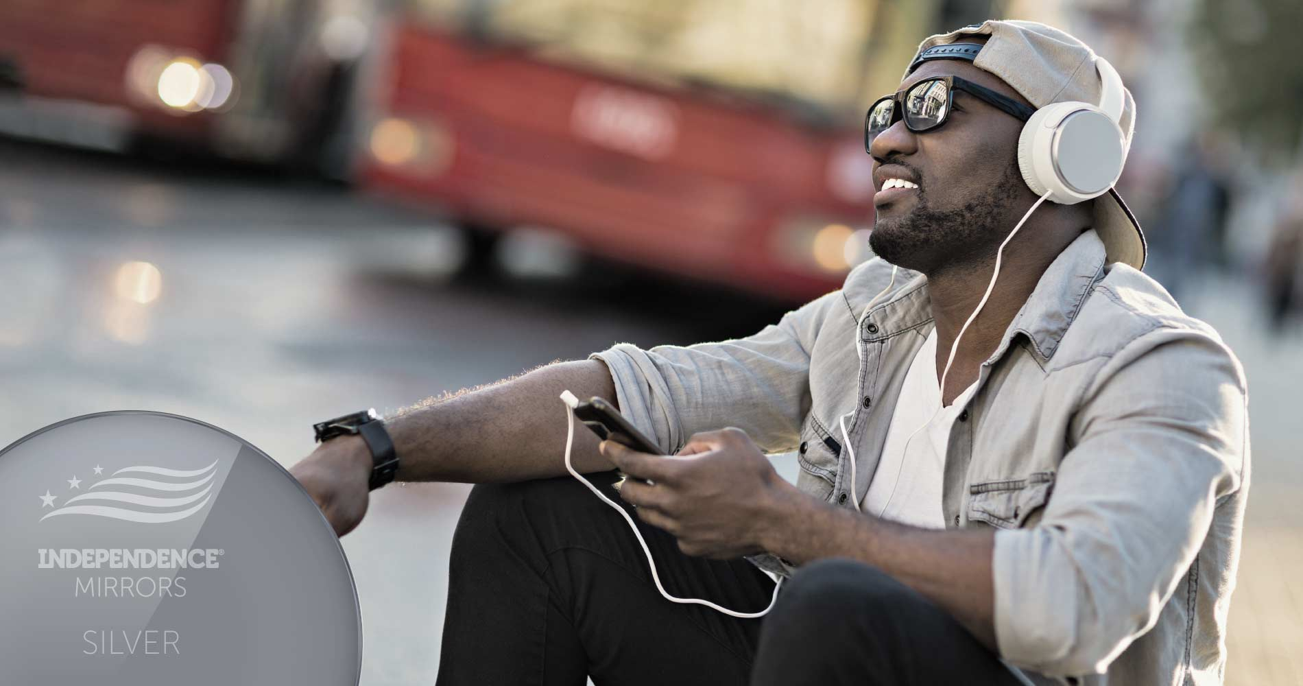 Man sitting on the curb listening to music with headphones, wearing silver-colored mirrored sunglasses