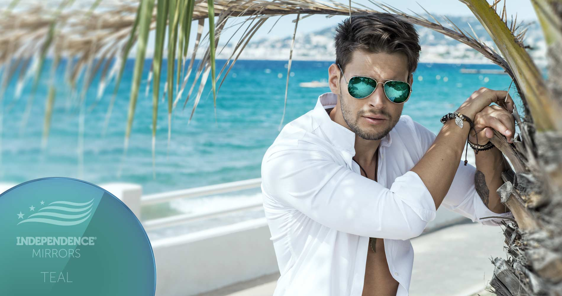 Man standing underneath a palm tree on the beach, wearing teal-colored mirrored sunglasses