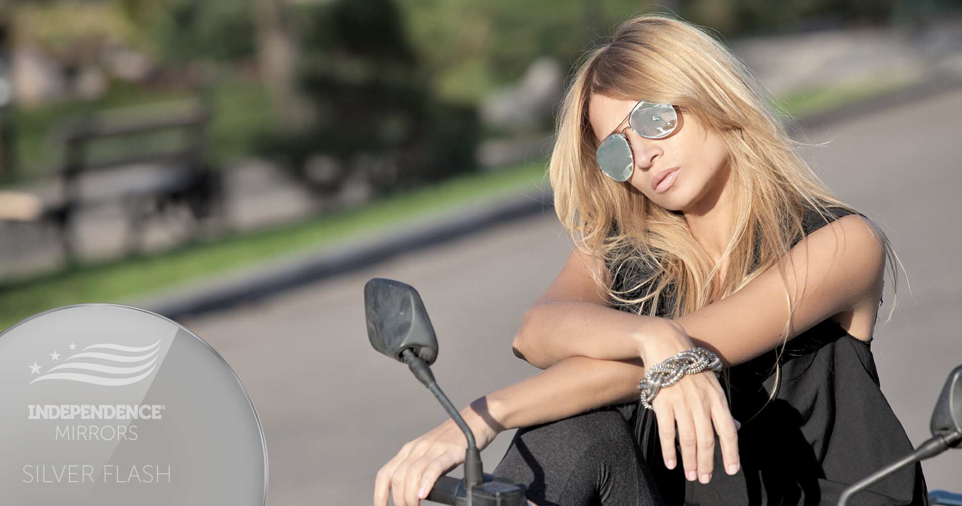 Woman sitting on a motorcycle, wearing silver flash-colored mirrored sunglasses