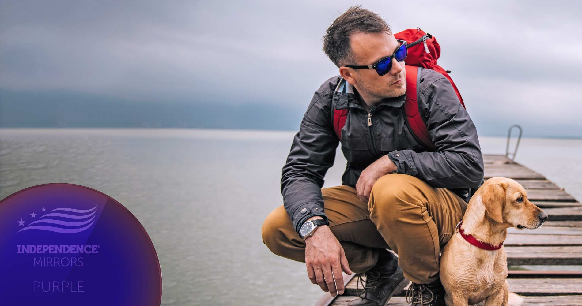 Man with hiking gear crouched down on a pier with a dog, wearing purple-colored mirrored sunglasses